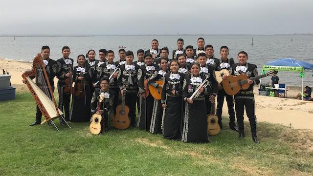 Mariachi students standing on shore