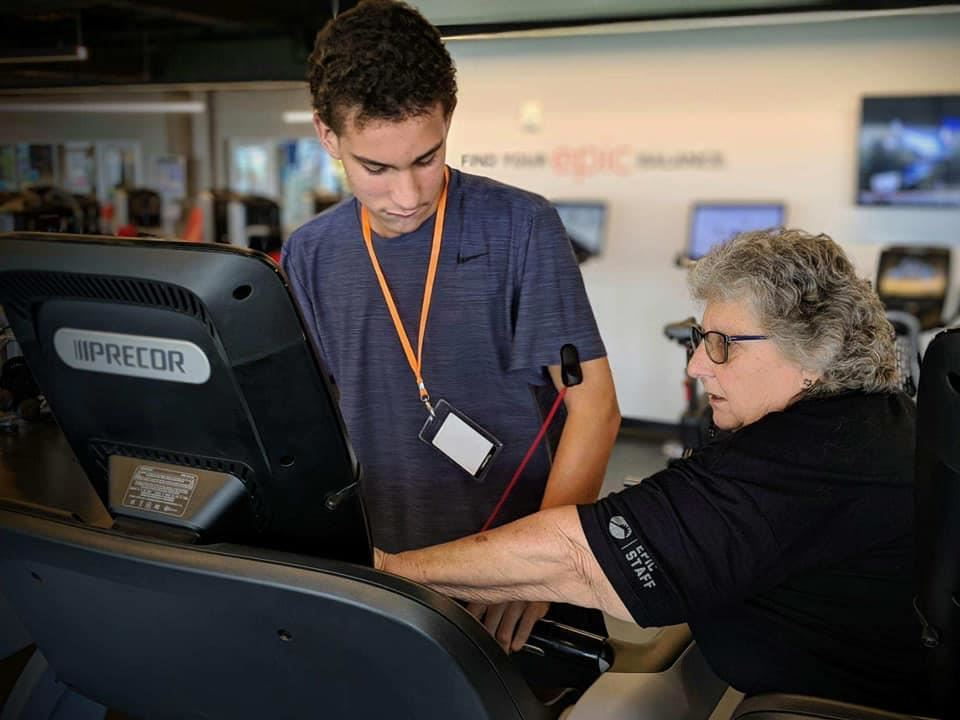 adult man working with a trainer on a treadmill