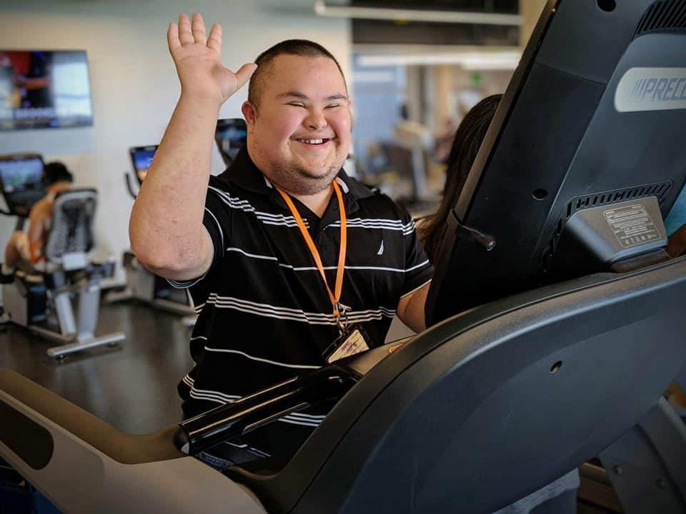adult man waving and smiling from treadmill