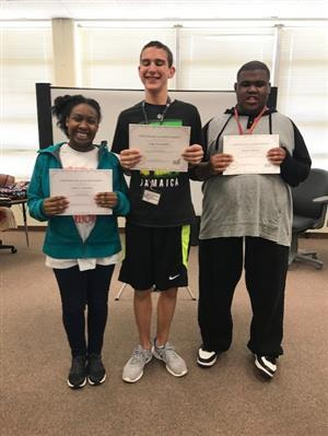 three students holding certificates