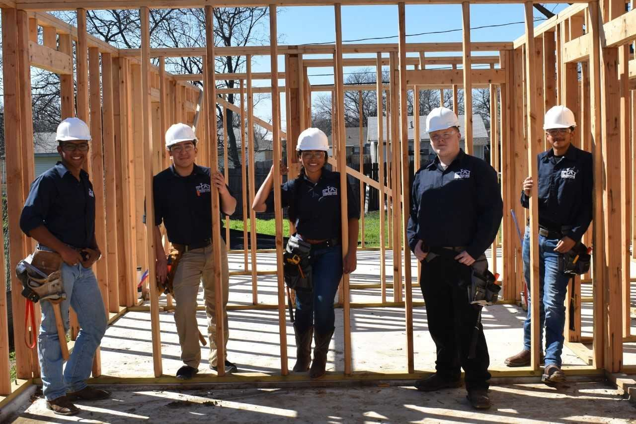 Gopher Construction Technology students on a house build site, standing with hard hats on in the frame.