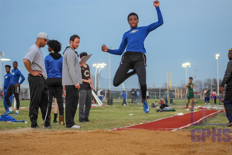 Gopher track and field athlete in the air for his long jump.
