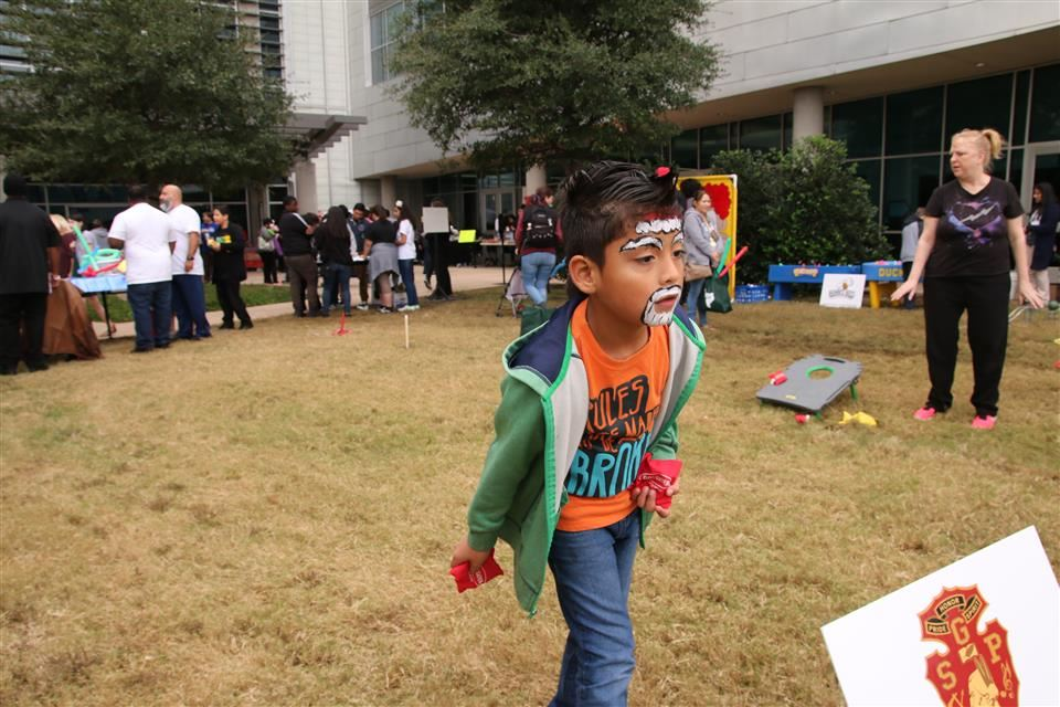 young boy with his face painted throwing a bean bag