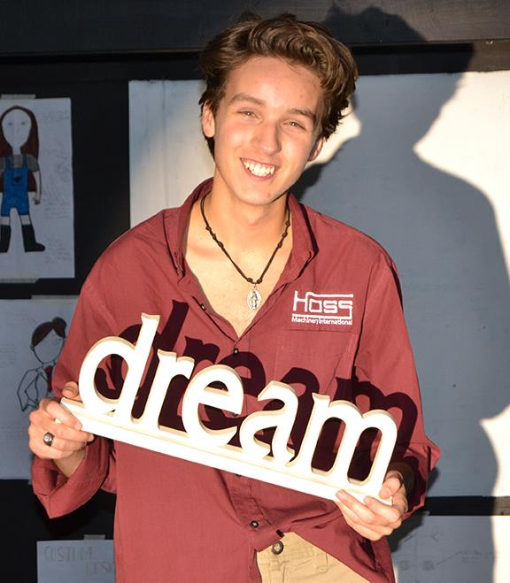 "Fabian in spotlight holding a sign that says ""dream"""