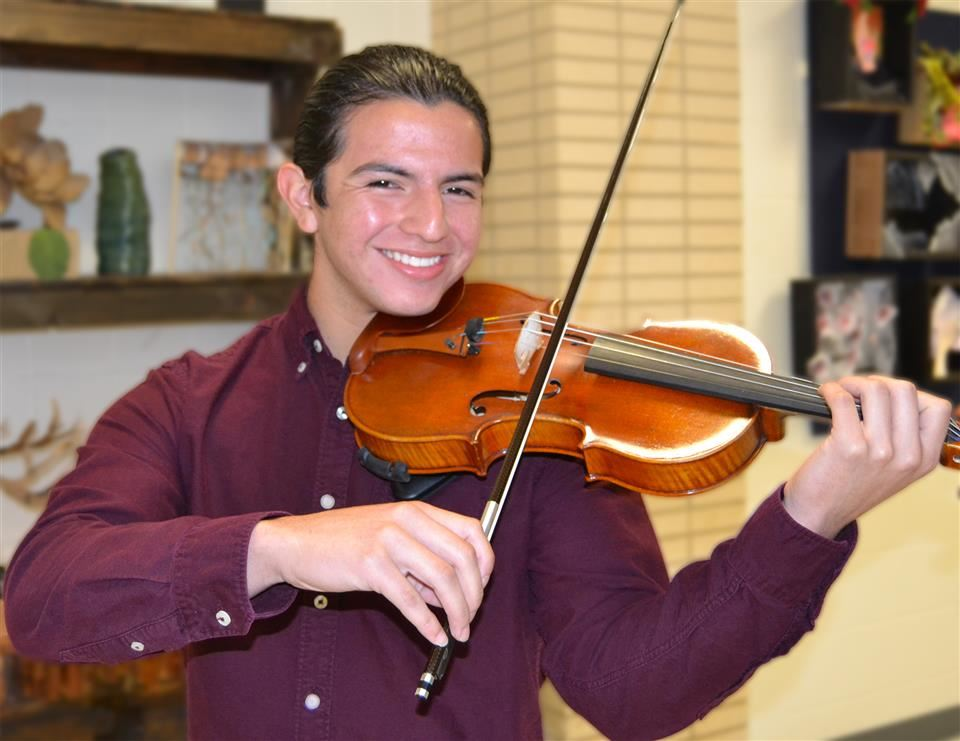 Nathan smiles while holding his violin