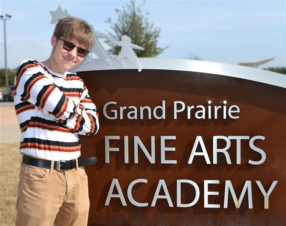 Triston standing outside by GPFAA sign, silver on copper
