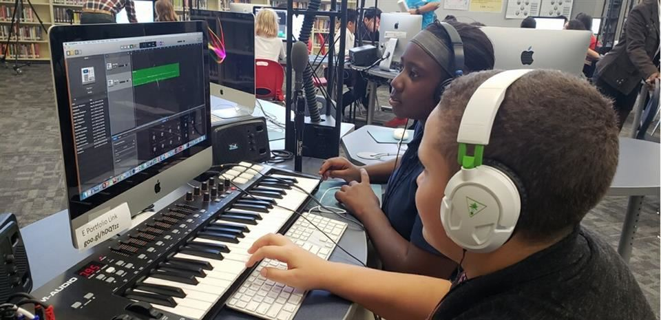 students wearing headphones at a keyboard lab and computer screen