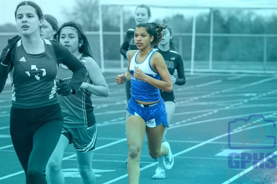 Lady Gopher track runner in a race.
