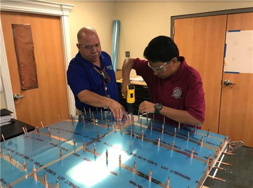 GPCI Instructor guides scholar in working on airplane wing