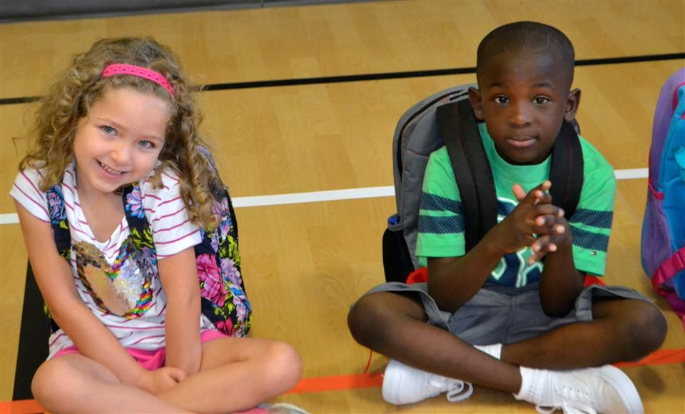Young girl and young boy sitting on gym floor on the first day of school.
